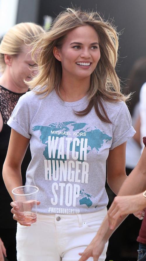 "Teigen on set for Michael Kors' ""Watch Hunger Stop"" campaign. Image Credit: Just Jared"