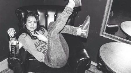 Black and white photo of Mitski lounging on a chair with her legs in the air and holding a bottle of alcohol in her right hand. She is looking at the camera.