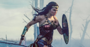 Action shot of Wonder Woman from the torso upwards, shield held out in front of her with her left hand. She is running through a battlefield.
